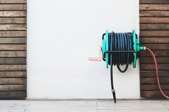 Background of a garden hose reel fixed on the wall. Blank wall on center with wooden boards decoration Royalty Free Stock Photography