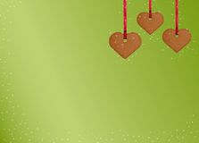 Background with gingerbread cookie hearts. Three gingerbread cookie hearts and stars on green background Stock Photos