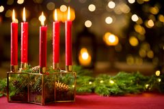 Background of glass and gold candleholder. With red candles and spruce branches on red table cloth. Living room decorated with lights and candles and Christmas royalty free stock photography