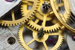 Background with golden metal cogwheels inside clockwork. Stock Photos