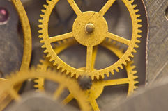 Background with golden metal cogwheels inside clockwork. Macro. Stock Image