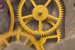 Background with golden metal cogwheels inside clockwork. Macro. Stock Image