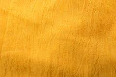 Background of a golden silk. Golden crumpled fabric texture closeup Stock Images