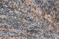 Background of granite stone close-up. On gray background, there are inclusions of pink mineral Stock Photo