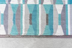 Background graphic, top view of a geometric rug with blue and grey color patterns, on top of a beige carpet, as a design element. In home decor stock photo