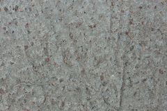 Background from concrete with impregnations from red granite gravel with an uneven surface. Background from gray concrete with impregnations from red granite Royalty Free Stock Photography