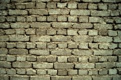 Background of a gray, old brick wall, built on clay royalty free stock photo