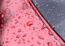 Water from rain drops beading on gray and red surface