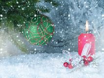 Green ball on a branch and a candle on a frozen stack background. Background with a green Christmas tree on a branch and a red candle Stock Images