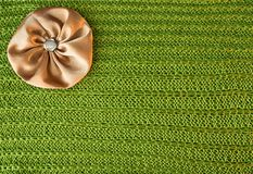 Background with a green knit texture and brown bow Stock Photos