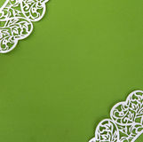 Background of green paper with corners made of white lace stock photos