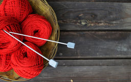Background of grey wood and clews. Basket with red clews and knitting needles on grey wood Stock Photography