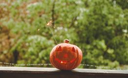 Background Halloween pumpkin on a cozy window sill with a red plaid. Whole pumpkin and sparkler outdoors. Happy Halloween! Autumn stock image