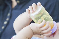 Background hand of baby suck orange juice Stock Photography