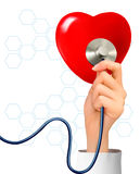 Background with hand holding a stethoscope against Royalty Free Stock Photography