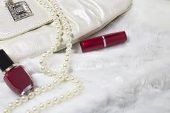 Background. Handbag, nail varnish, lipstick, necklace on white fur rug stock images