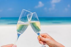 Champagne glasses in hands on beach background. Romantic honeymoon background