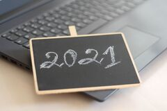 2021 background. Handwritten by chalk number of New year 2021. Hand drawn chalk lettering on blackboard. Playing with Laptop.