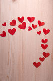 Background of hearts for valentine's day. Small red hearts on a wooden table lined Stock Image