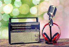 Microphone, radio and headphones on wooden table. Background holiday equipment sign studio style old Stock Photo