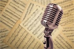 Retro style microphone on notes background. Background holiday equipment sign studio style old Royalty Free Stock Photography