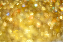 Background of holiday. Background of golden and colorful sparkles Stock Photos
