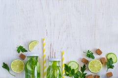 Background homemade lemonade bottles, cucumber, lime Royalty Free Stock Photos