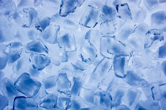 Background of ice cubes close up. Background with ice cubes in blue light Royalty Free Stock Photo