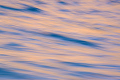 Background image of blur ocean waves with sunrise colors reflect. Abstract blur background of sunrise reflecting in ocean waves Stock Images