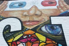 Old brick wall with bright and colorful art of woman in mask, Austin Texas, 2018. Background image of bright and colorful graffiti  painting of woman in mask, on royalty free stock images