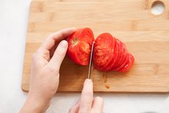 Slicing half tomato into slices on the kitchen Board stock image