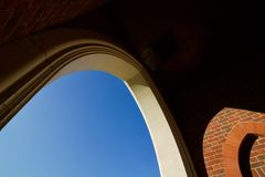 Sky visible through white arch beside brickwork - image stock images