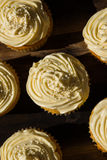 A background image of five delicious cream colored cupcakes on a wooden board.  Royalty Free Stock Photography
