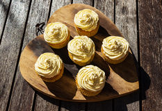 A background image of five delicious cream colored cupcakes on a wooden board.  Royalty Free Stock Image