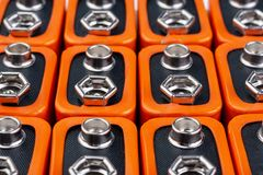 Background image of a large number of orange batteries, standing in several rows.  royalty free stock image