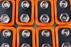 Background image of a large number of orange batteries, standing in several rows.  stock photo
