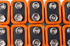 Background image of a large number of orange batteries, standing in several rows.  royalty free stock images