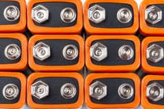 Background image of a large number of orange batteries, standing in several rows.  royalty free stock photography