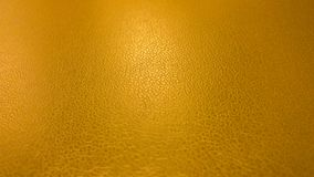 Gold Leather Textured Background APC_0138. Background image of leather texture in gold color. Camera focused in the middle with radial light in the center. Great Royalty Free Stock Image