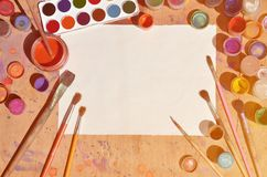 Background image showing interest in watercolor painting and art. A blank sheet of paper, surrounded by brushes, cans with waterc. Olor paint and gouache, which royalty free stock images