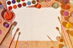 Background image showing interest in watercolor painting and art. A blank sheet of paper, surrounded by brushes, cans with waterc. Olor paint and gouache, which stock photos