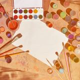 Background image showing interest in watercolor painting and art. A blank sheet of paper, surrounded by brushes, cans with waterc. Olor paint and gouache, which stock image