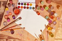 Background image showing interest in watercolor painting and art. A blank sheet of paper, surrounded by brushes, cans with waterc. Olor paint and gouache, which stock images