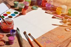 Background image showing interest in watercolor painting and art. A blank sheet of paper, surrounded by brushes, cans with waterc. Olor paint and gouache, which stock photo