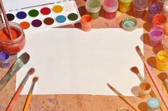 Background image showing interest in watercolor painting and art. A blank sheet of paper, surrounded by brushes, cans with waterc. Olor paint and gouache, which royalty free stock photography