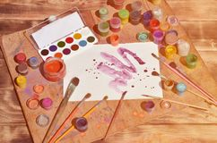 Background image showing interest in watercolor painting and art. A painted sheet of paper, surrounded by brushes, jars of waterc. Olor paint and gouache, which stock images