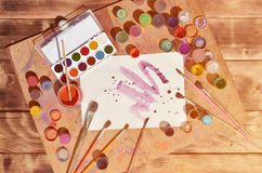 Background image showing interest in watercolor painting and art. A painted sheet of paper, surrounded by brushes, jars of waterc. Olor paint and gouache, which royalty free stock image