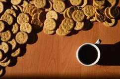 Background image of a small white cup of coffee and classic salty cracker on a brown wooden table with copyspac. E Royalty Free Stock Image