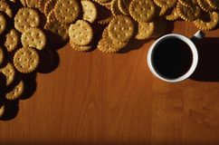 Background image of a small white cup of coffee and classic salty cracker on a brown wooden table with copyspac. E Stock Photography
