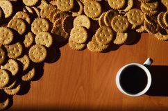 Background image of a small white cup of coffee and classic salty cracker on a brown wooden table with copyspac. E Stock Photos